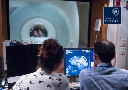 Researchers in the MRI scanner control room looking at an image of a brain on the screen.