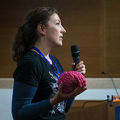 Sarah Finnegan holding a microphone presenting